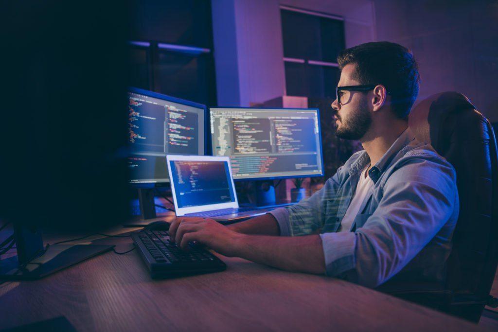 Programmer concentrating on his work, while using multiple computer screens.
