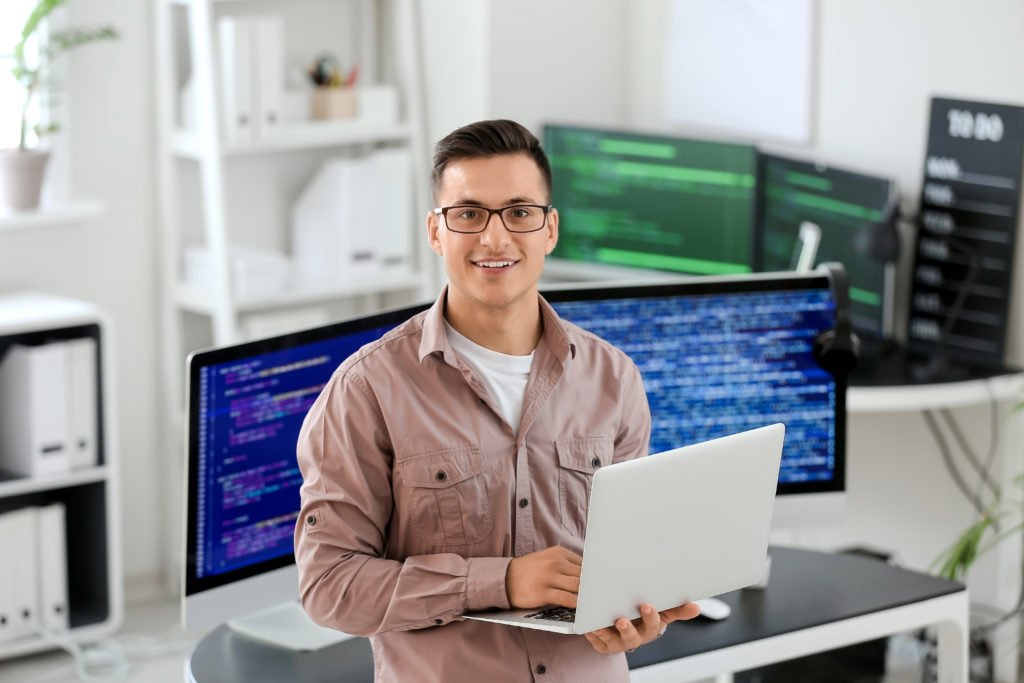 Programmer in glasses with laptop and computer monitors inside the office.