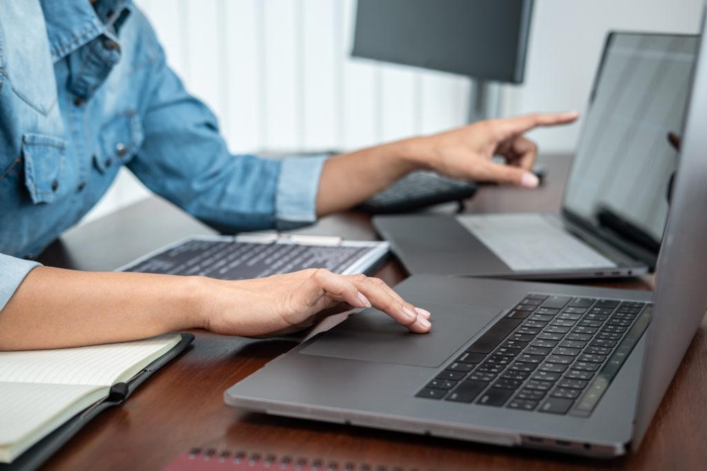 Woman using multiple laptop screens.
