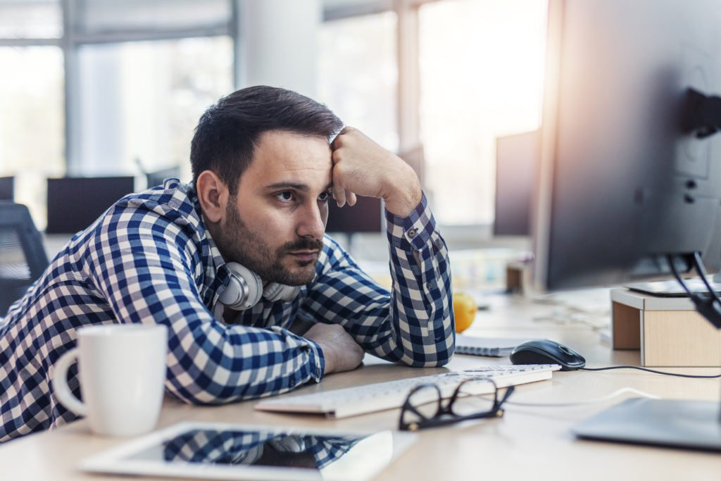 Programmer looking stressed while looking at codes on the monitor.