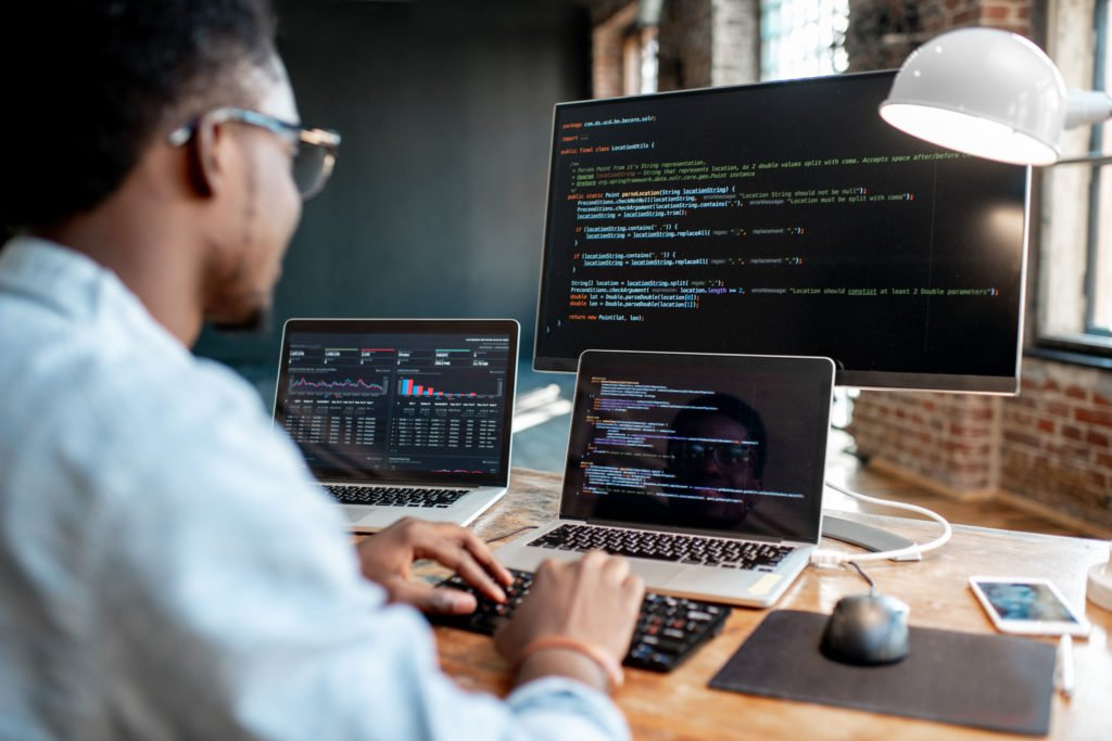 Programmer working with program codes using three monitors.
