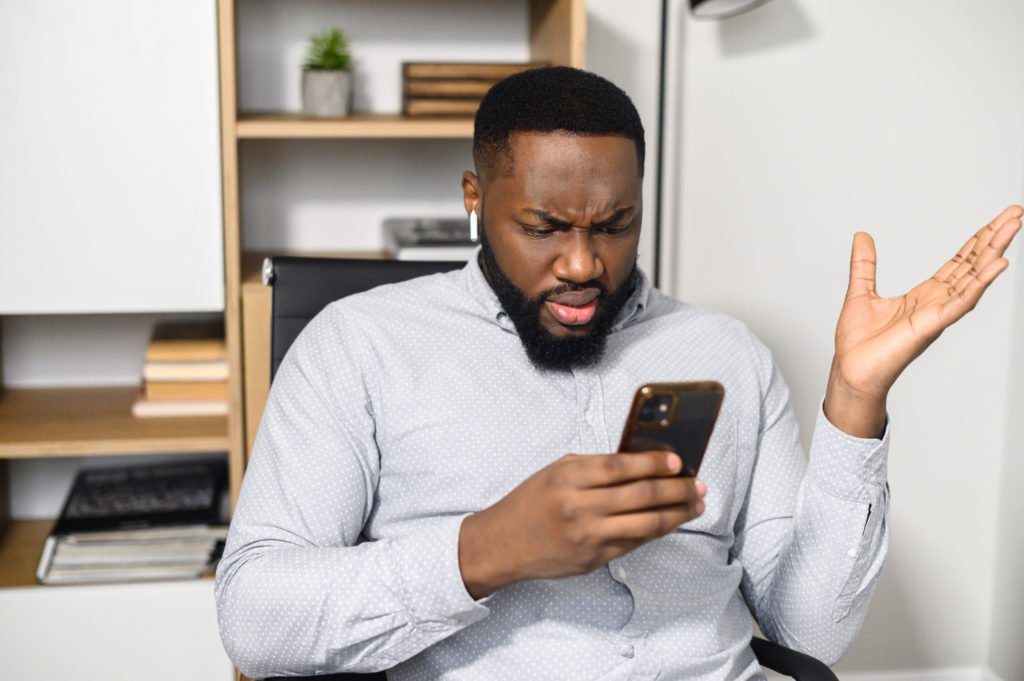Guy in casual shirt holding his smartphone with a puzzled expression.