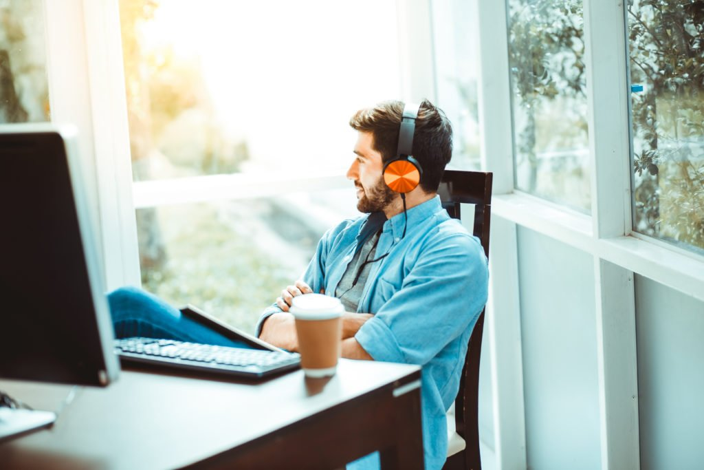Relaxed man drinking coffee and listening to music while working from home.