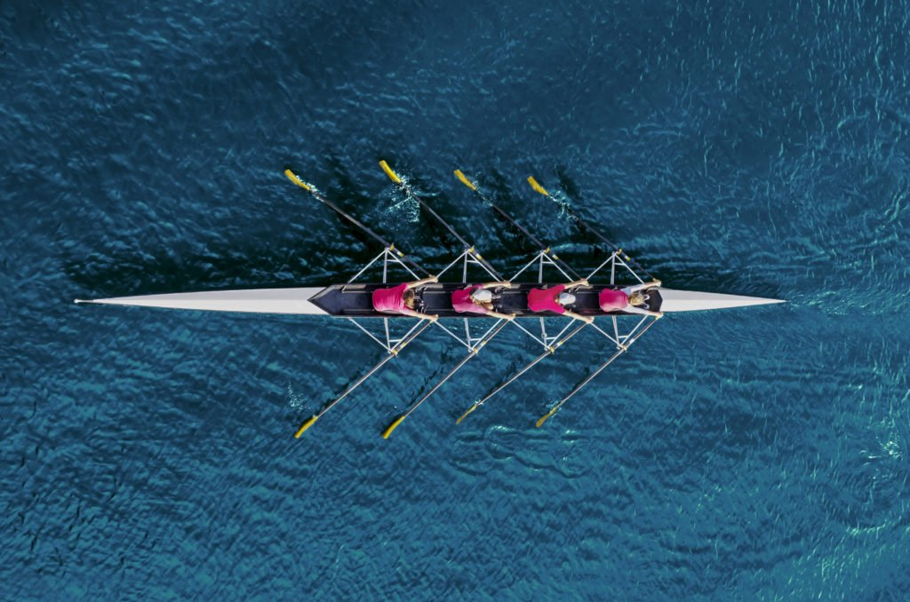 Women's rowing team on blue water, top view.