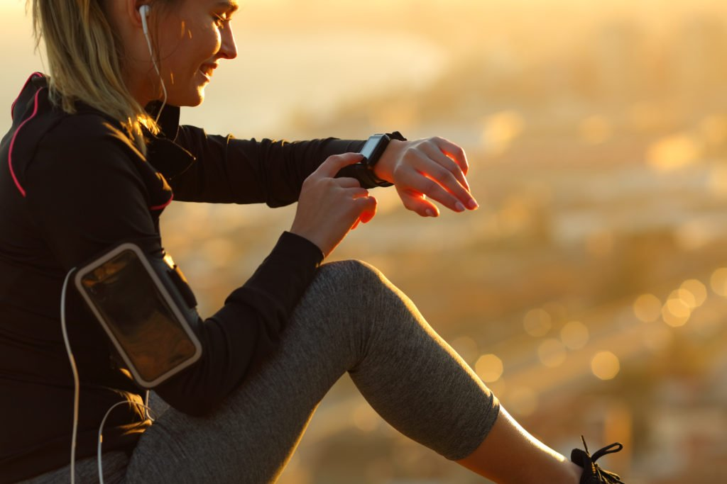 Runner with earphones resting and looking at her smartwatch.