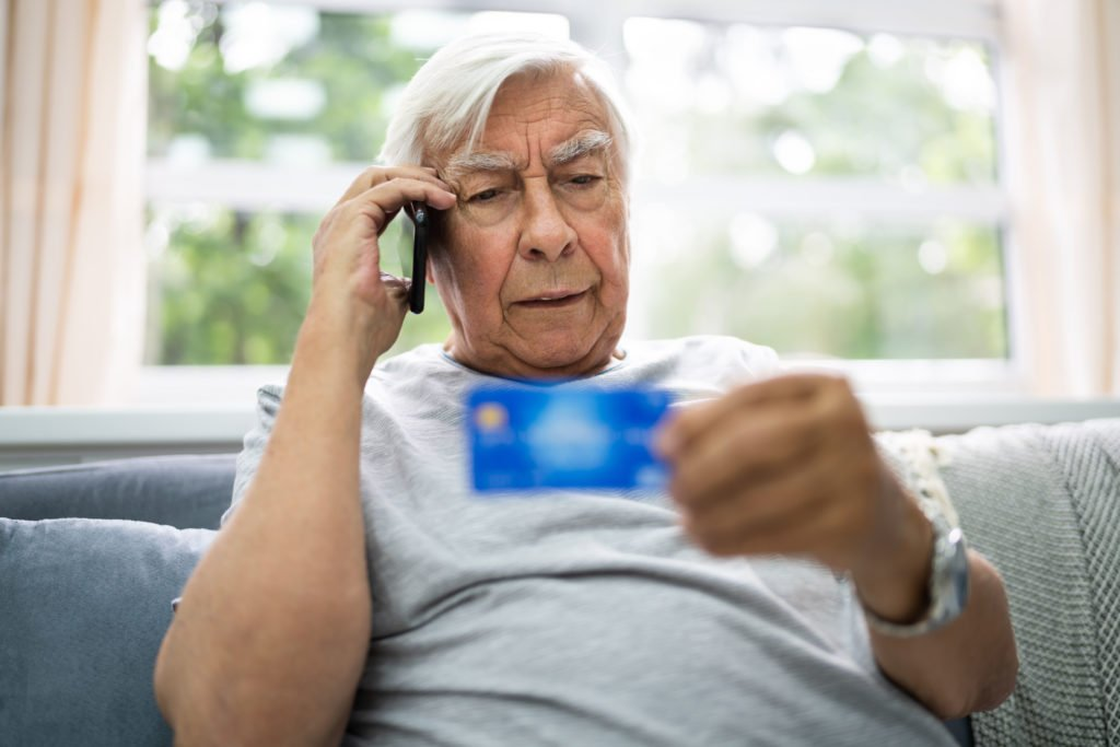 Senior man confused while taking a scam call.