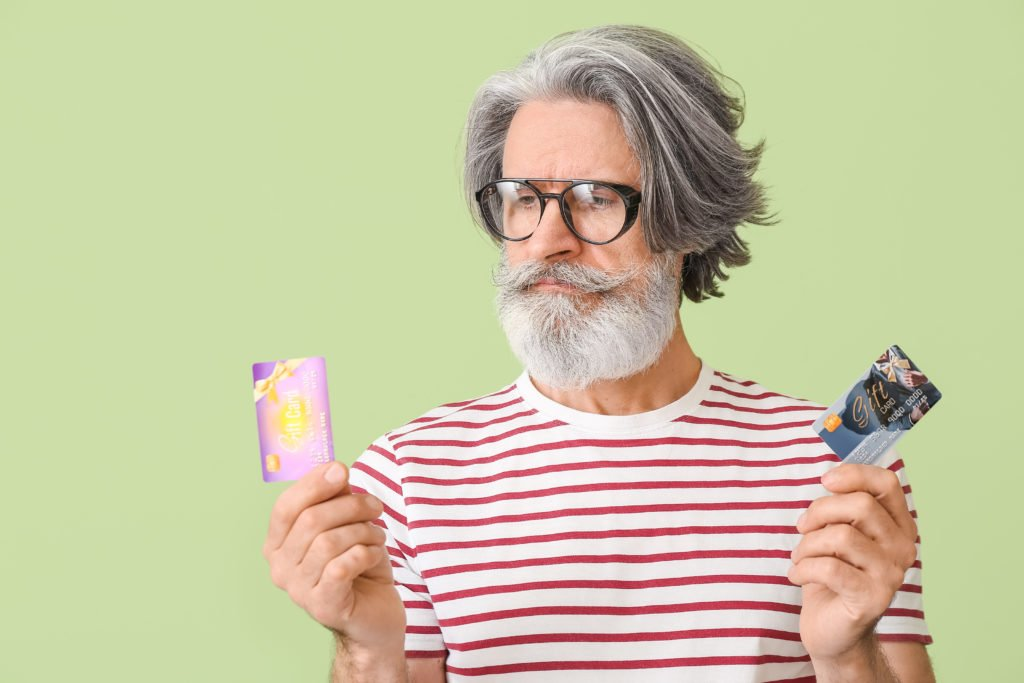 Senior man holding two gift cards, green background.
