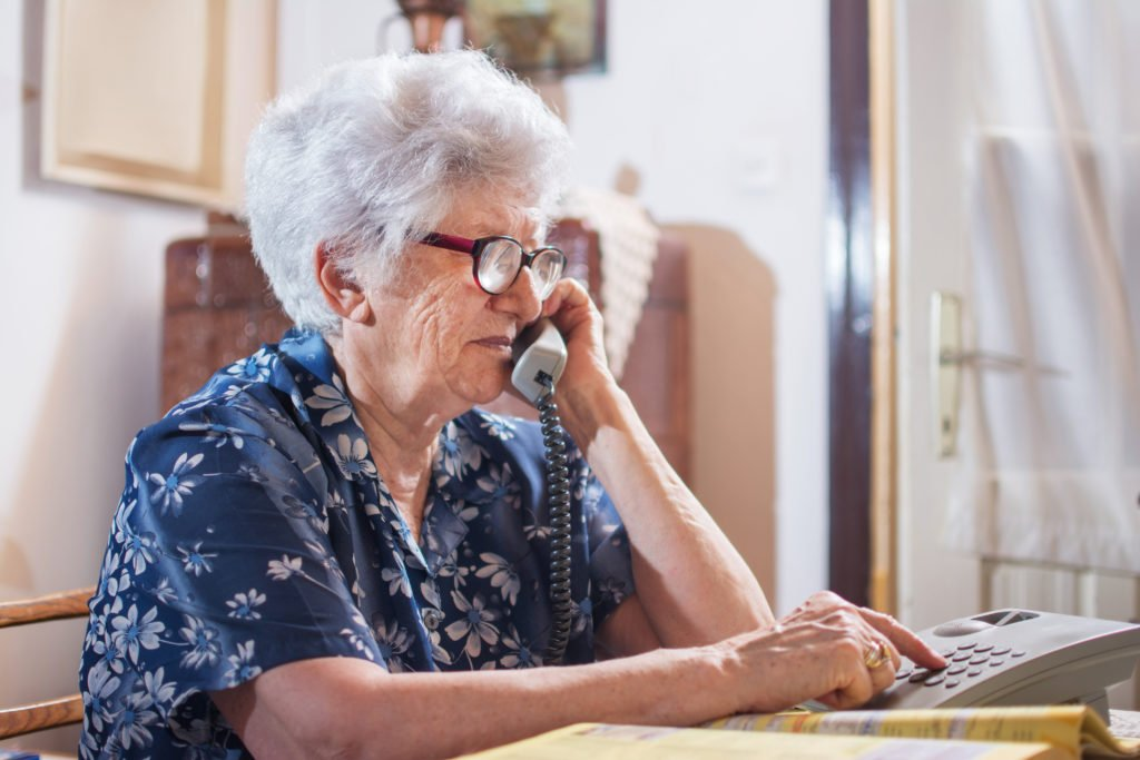 Senior woman dialing on the telephone.