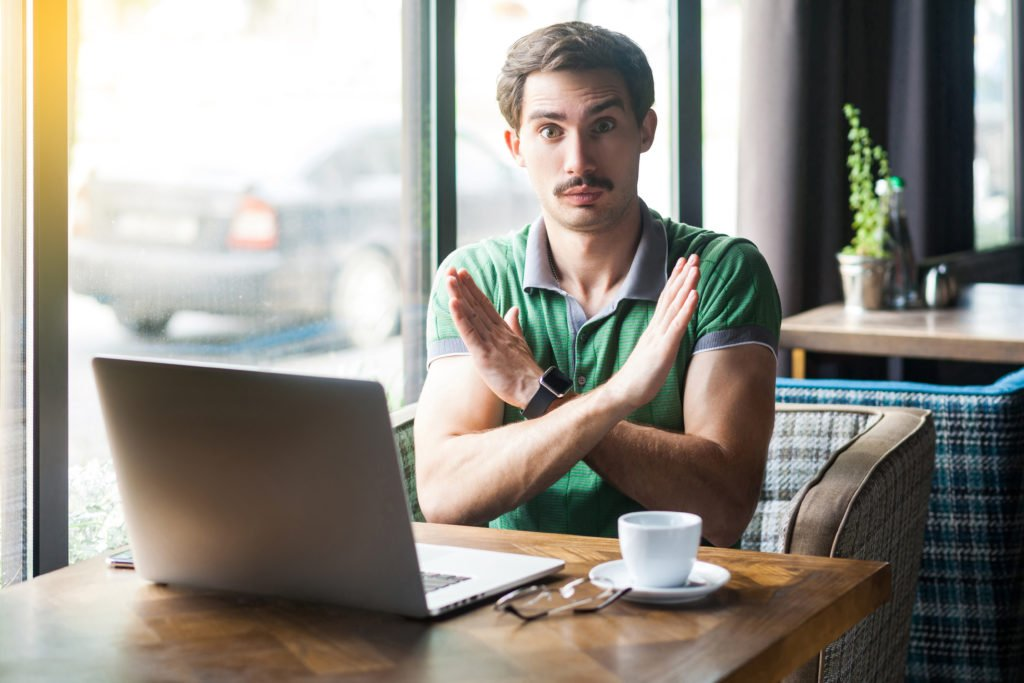 """Serious man in front of his laptop, doing a """"closed"""" sign with his arms."""