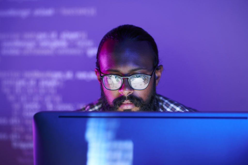 Serious programmer coding on computer with purple background.