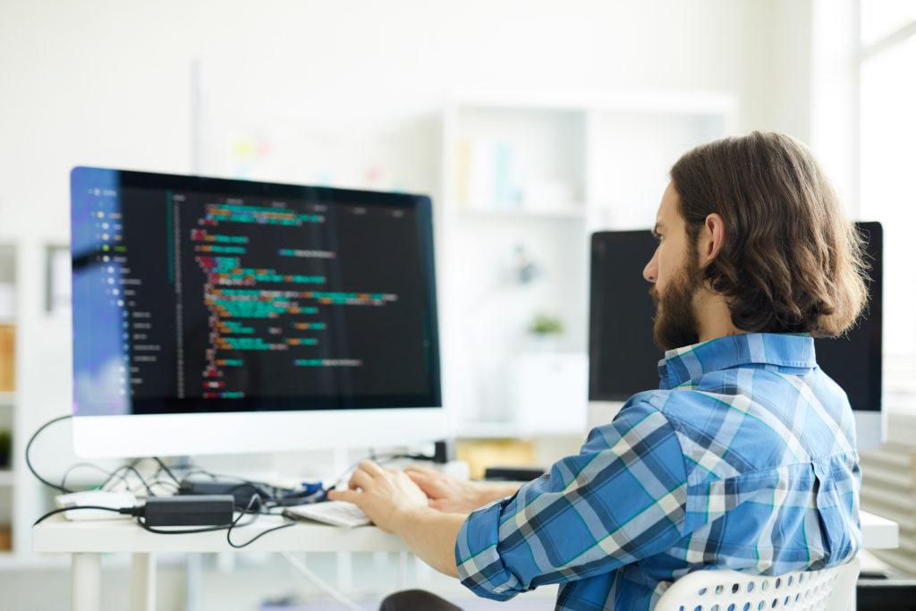 Serious programmer creating a computer software.