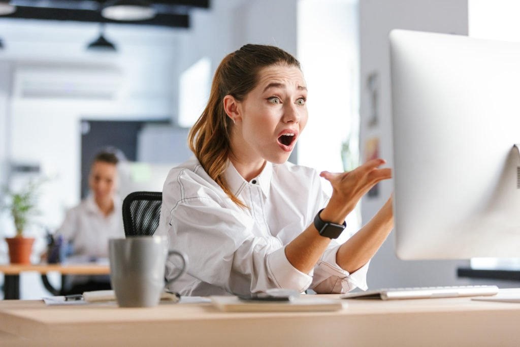 Shocked woman in front of computer, inside workplace.