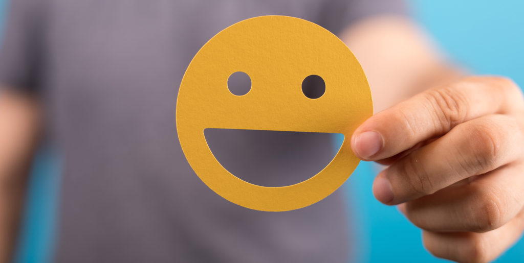 Man shows yellow smiley in the camera.