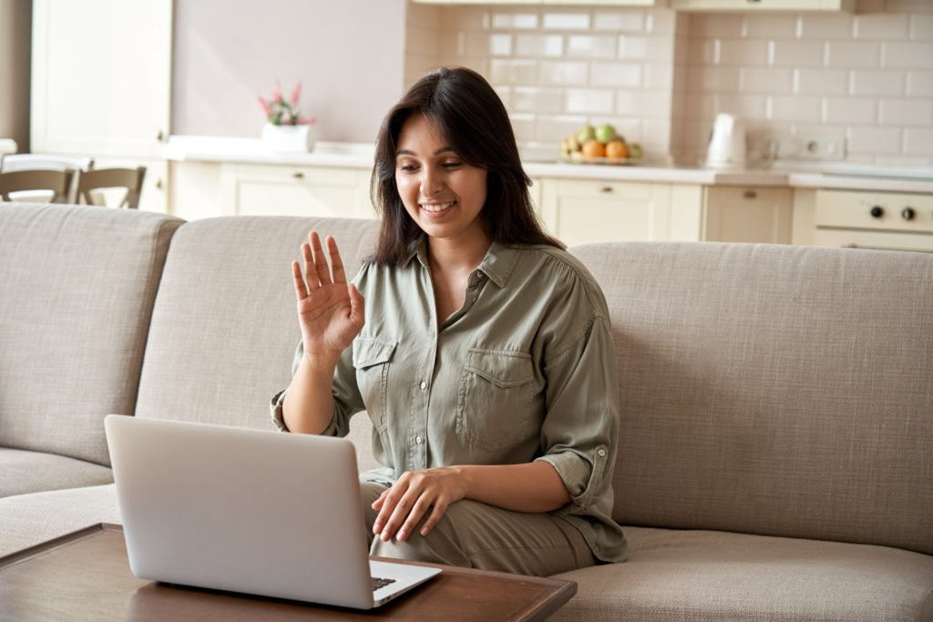Smiling young woman having an online videoconference.