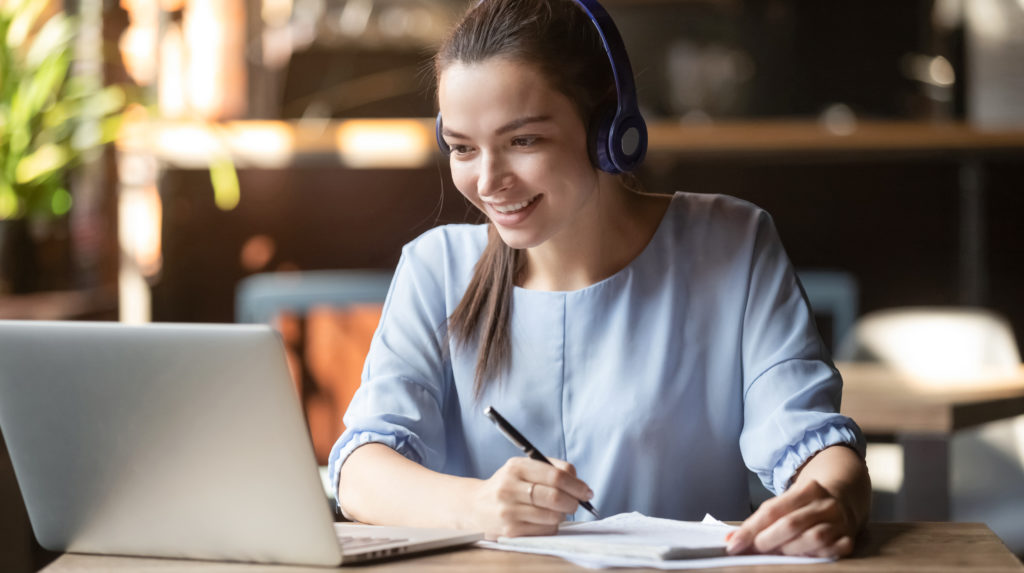 Smiling girl student wear wireless headphone study online with skype teacher, happy young woman learn language listen lecture watch webinar write notes look at laptop sit in cafe, distant education.