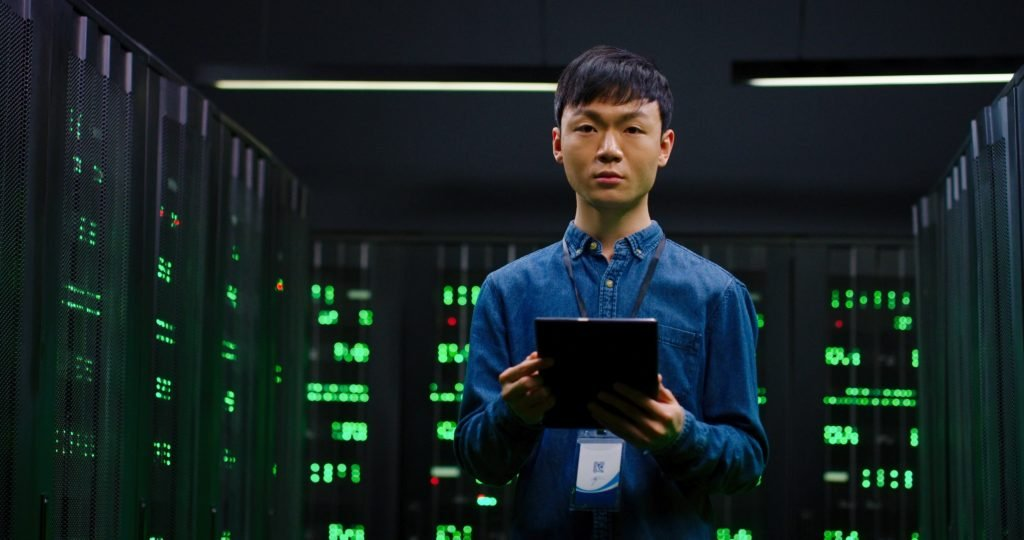 System administrator in a big data center standing among servers.