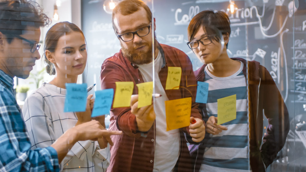 Team of developers brainstorming on a glass board.