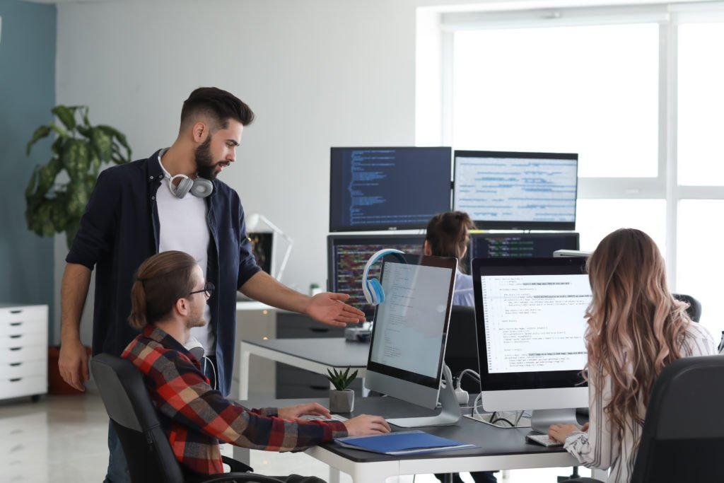 Team of programmers working with multiple computer screens inside the office.