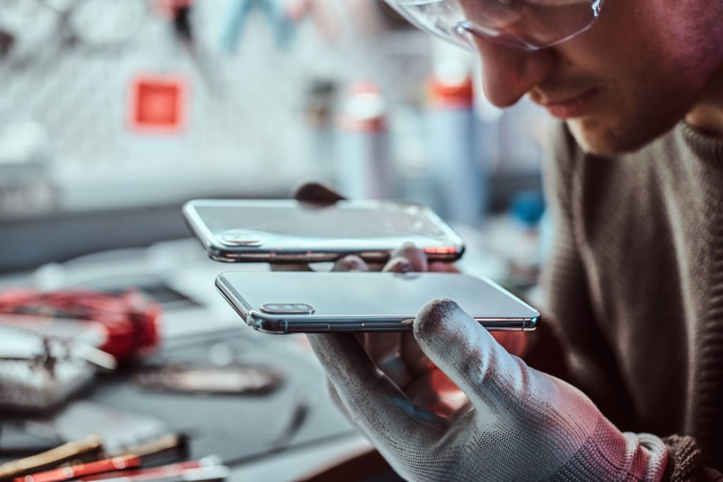 Technician comparing two smartphones for repair.