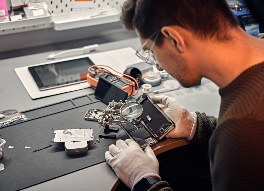 Technician inspecting smartphone parts using a magnifier.