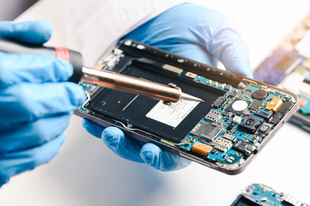 Technician repairing phone motherboard similar to a computer.