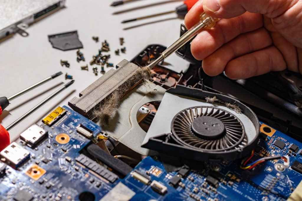 Technician repairs laptop and cleans dust to prevent from overheating.