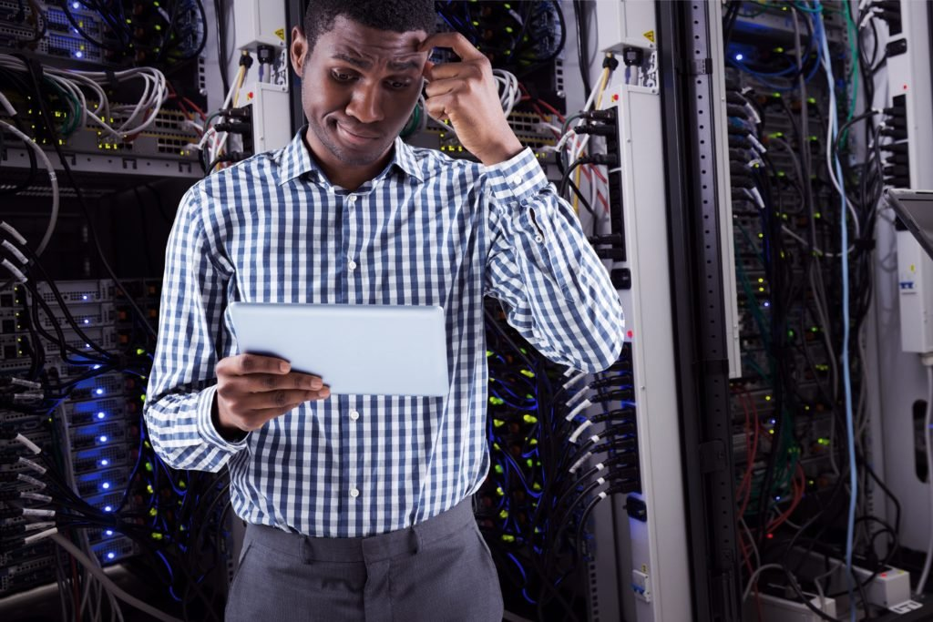 Technician thinking while holding a tablet.