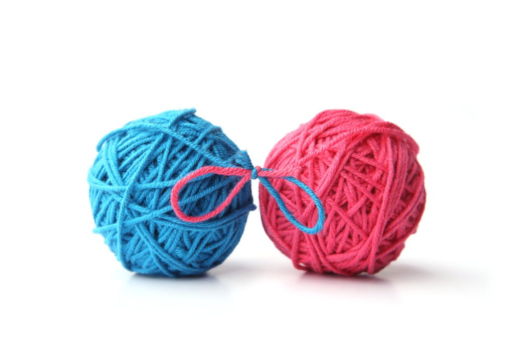 Two pink and blue cotton thread balls tied in bow isolated on white background. Different color pink and blue thread balls.