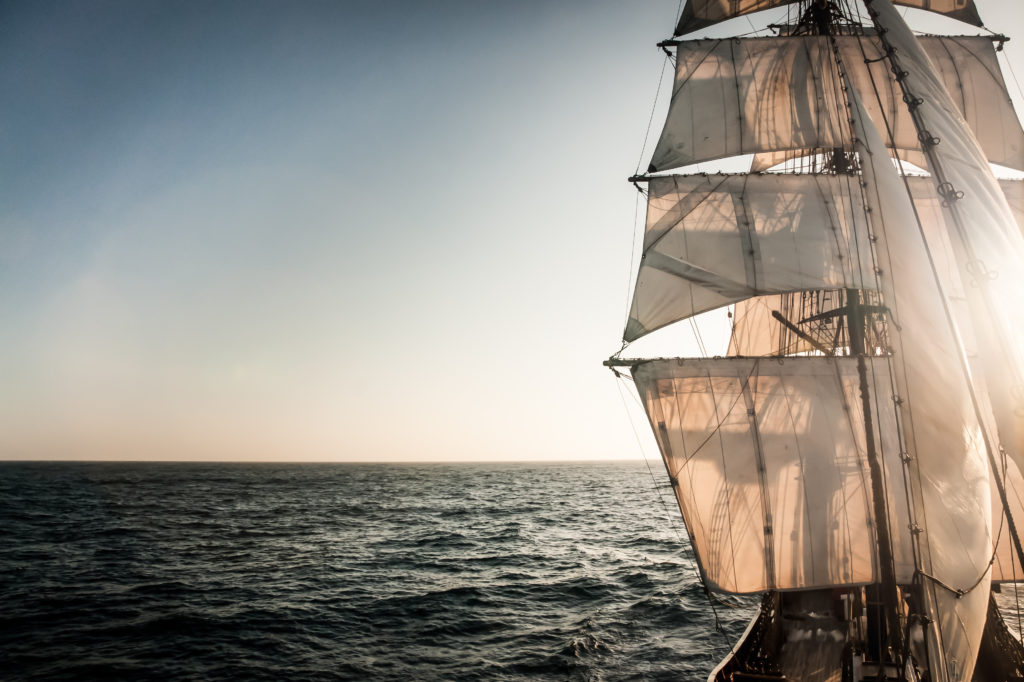 Backlit sails of a traditional tall ship on the atlantic.