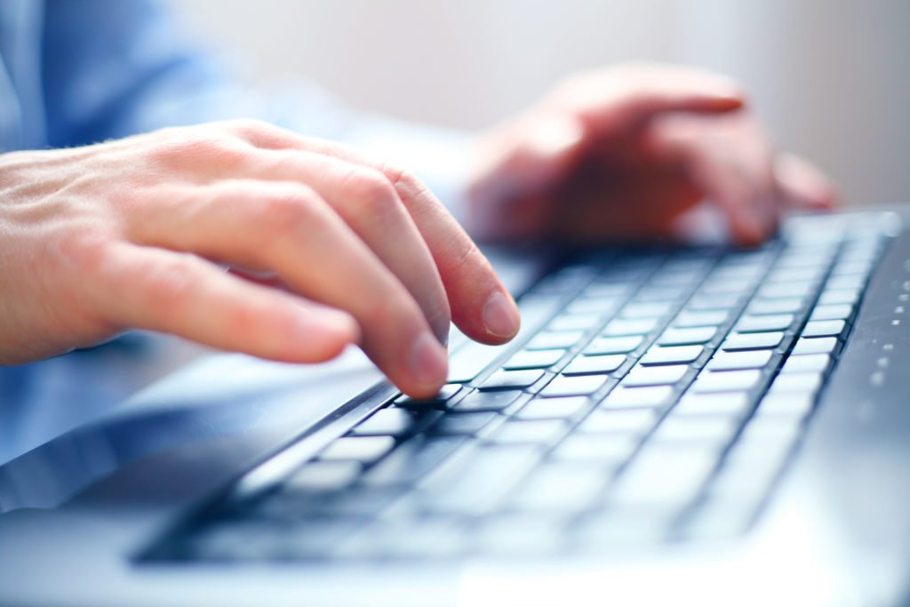 Close-up of hand typing on a keyboard, concept of an office job.