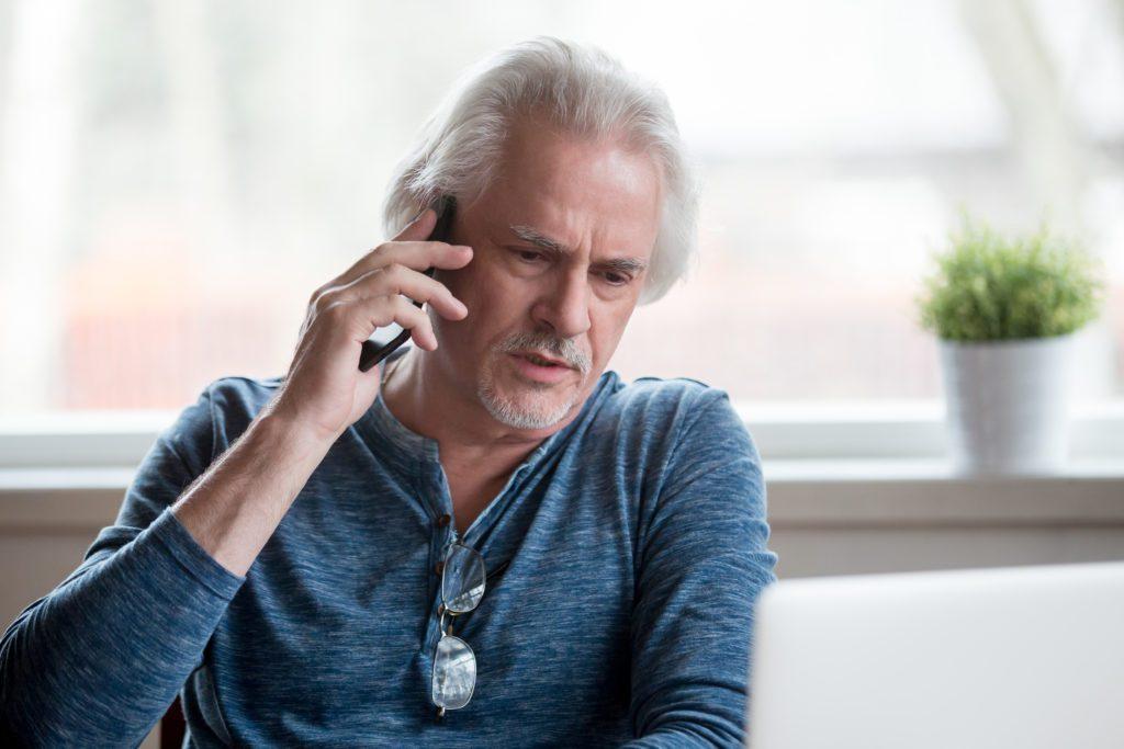 Unsatisfied senior man talking on his phone.