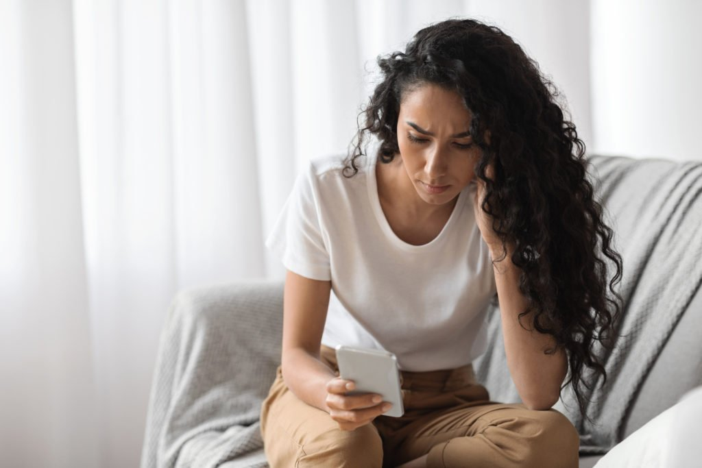 Upset woman looking at her phone at home.