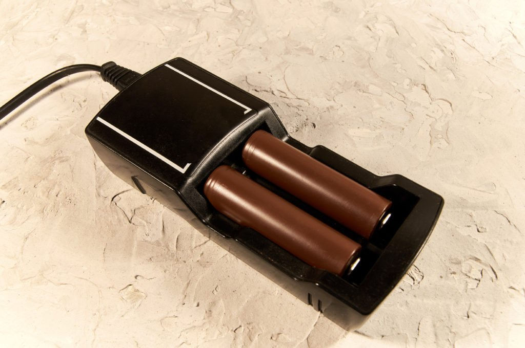 Black vape charger with two brown batteries.