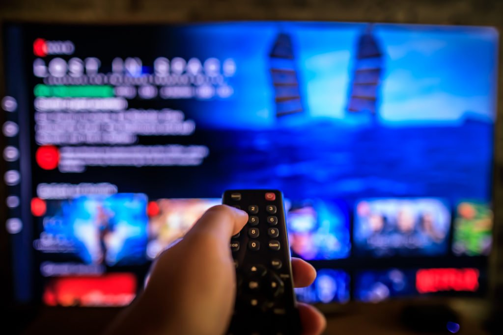 Video on demand television screen with remote control in hand.