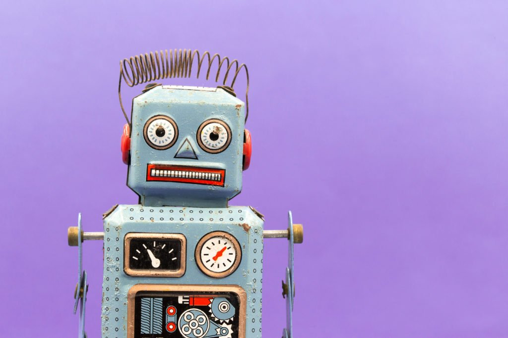 Vintage tin toy robot with purple background.