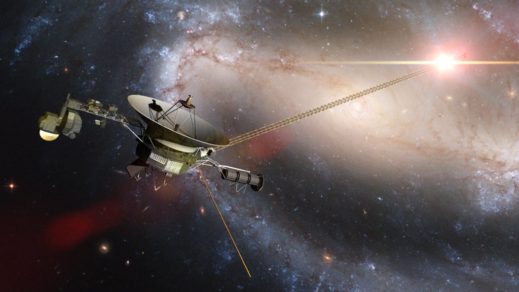 Voyager spacecraft in front of a galaxy.