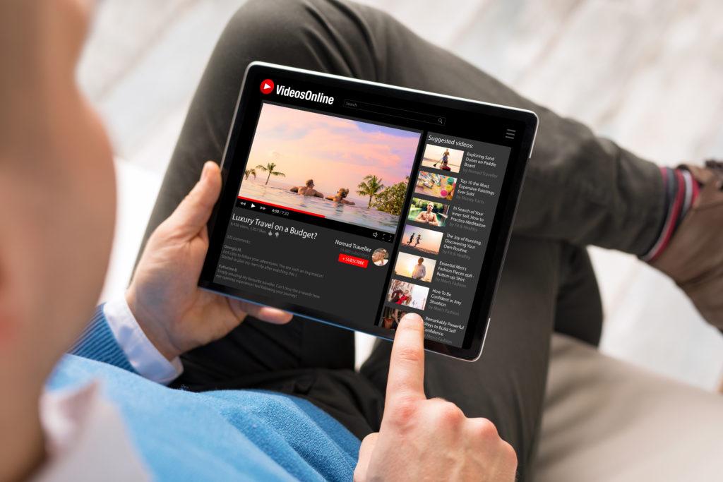 Man watching online videos on tablet.