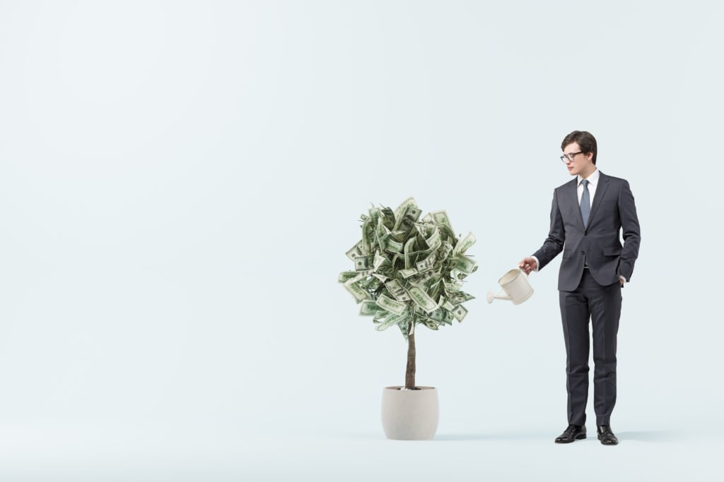 Businessman in a suit with a blue tie watering a small dollar tree. Blue room background. Concept of investment.