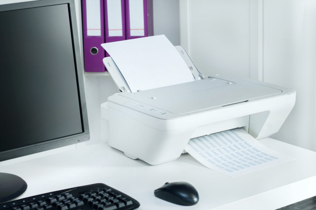 White printer with black computer.