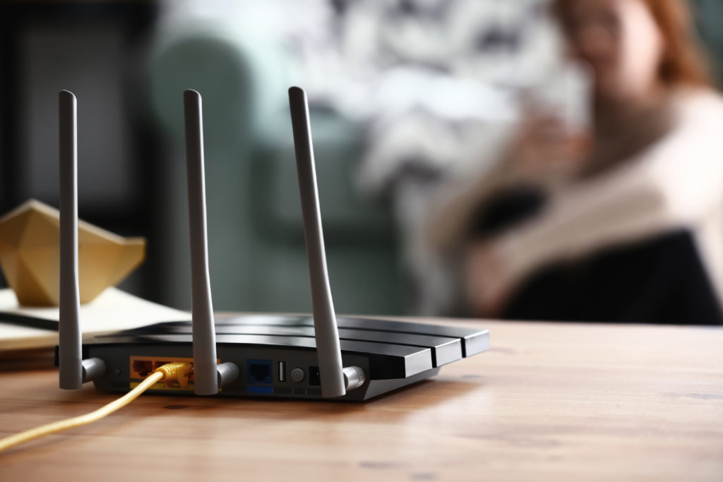 Modern wi-fi router on wooden table in room.