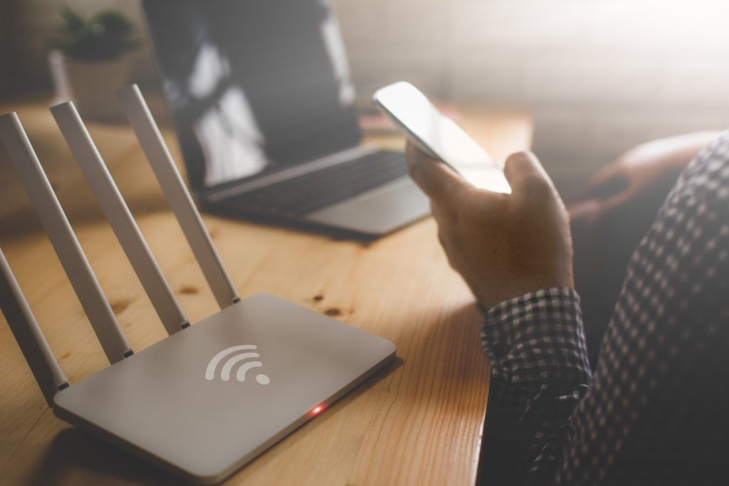 Close-up of a wireless router with a man using his smartphone and laptop.