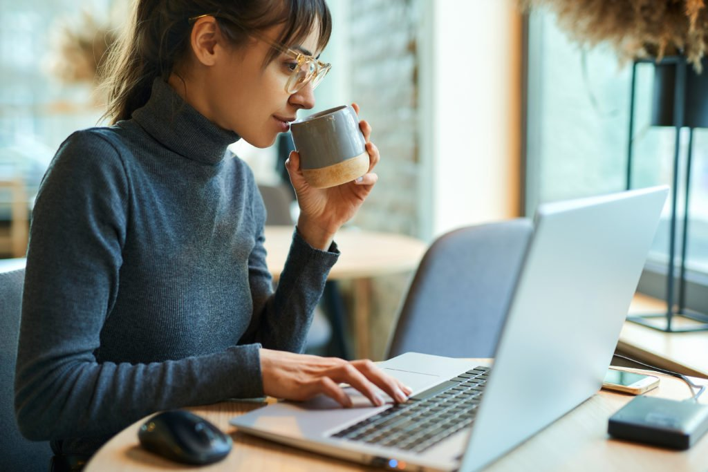 Young woman in eyeglasses enjoying coffee while working on portable laptop.