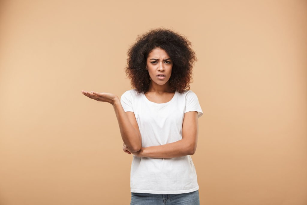 Portrait of a confused young african woman looking at camera isolated over beige background.