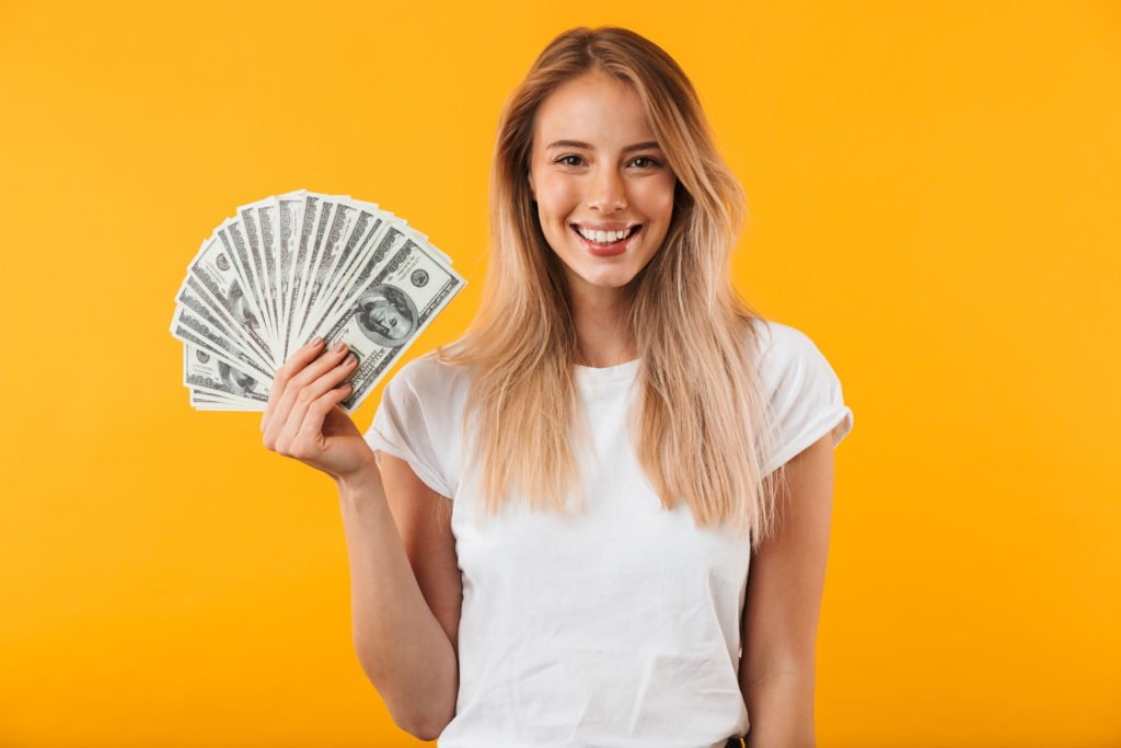 Portrait of a smiling young blonde girl showing bunch of money banknotes isolated over yellow background.