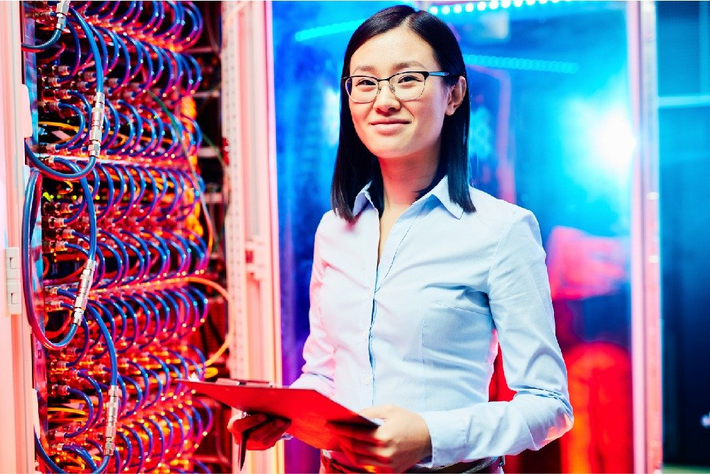 Researcher in supercomputer center in front of blinking ethernet lights.