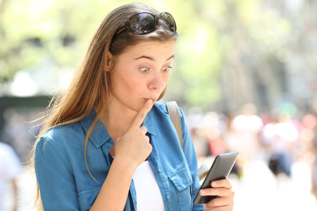 Woman with a shocked expression, making a mistake on her phone.