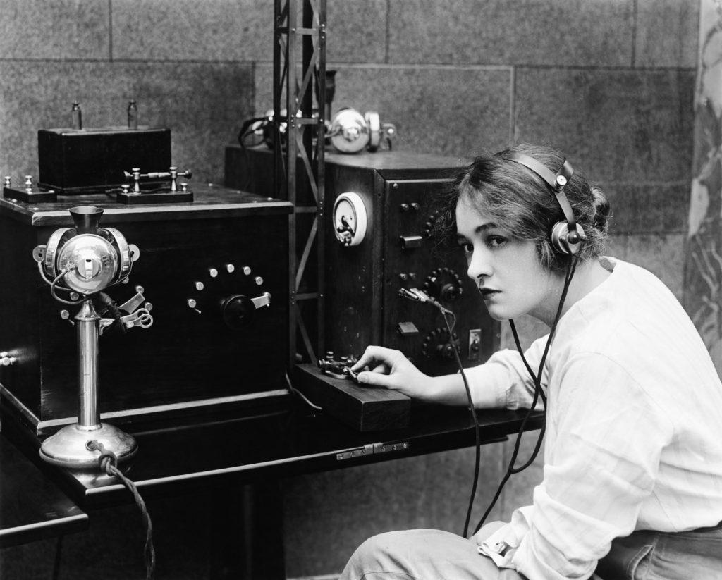 Woman sending morse code using a telegraph, old photograph.