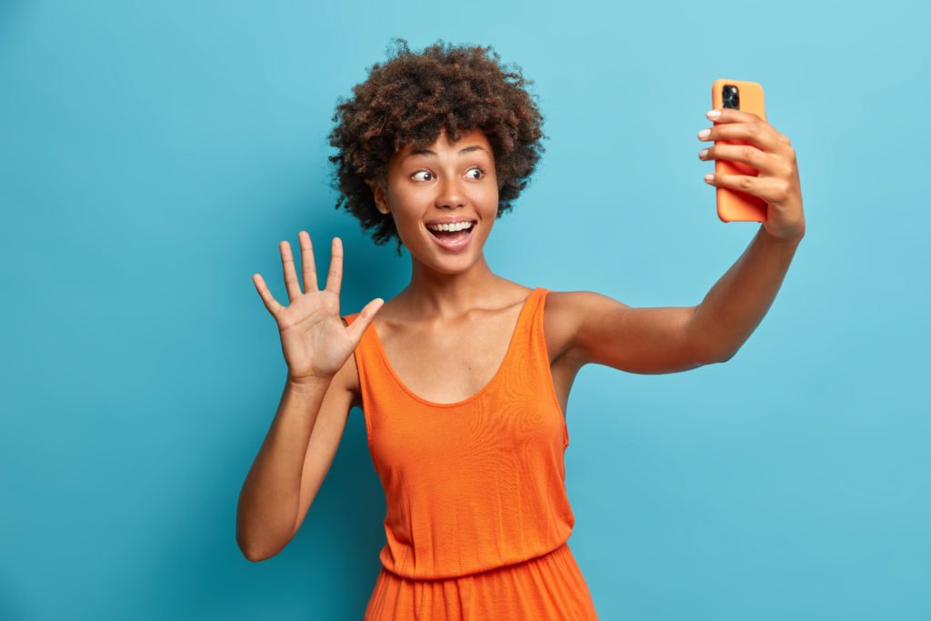 Woman in orange dress waving at her smartphone front camera.