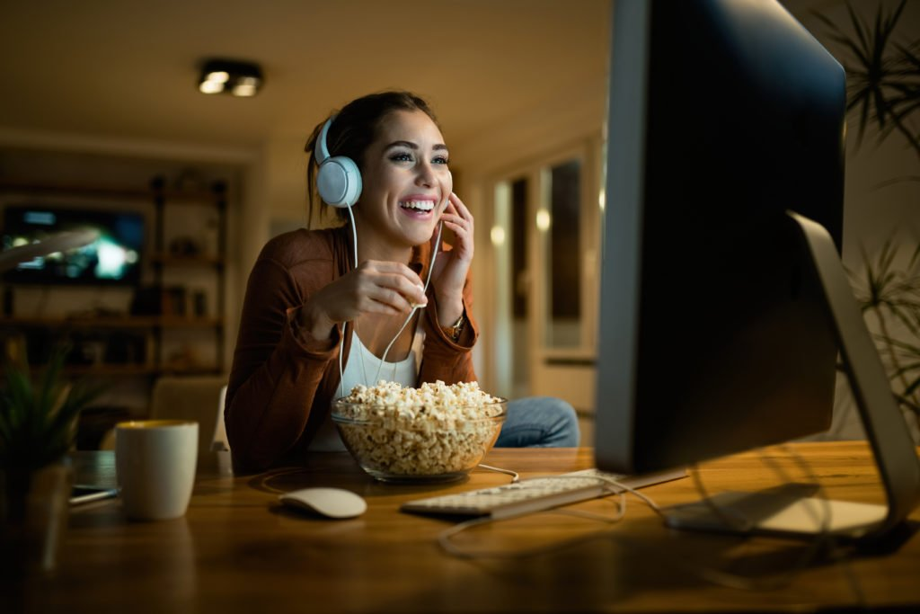 Young woman having fun while eating popcorn and watching movie on a computer.