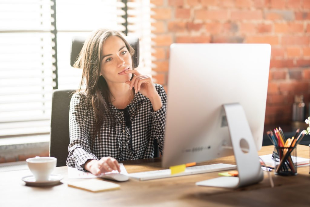 Woman thinking and working with big computer monitor at the office.